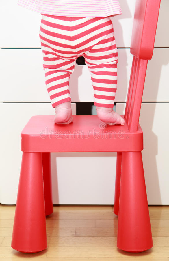 在婴孩椅子的儿童脚,孩子回家安全概念 库存图片