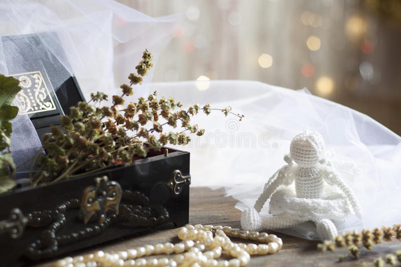 在黑小箱的天使和珍珠项链在五颜六色的背景bokeh 库存照片