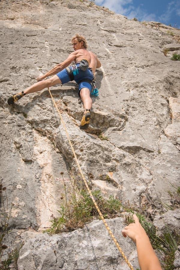 在绳索巩固的年轻成人上升的岩石 免版税图库摄影