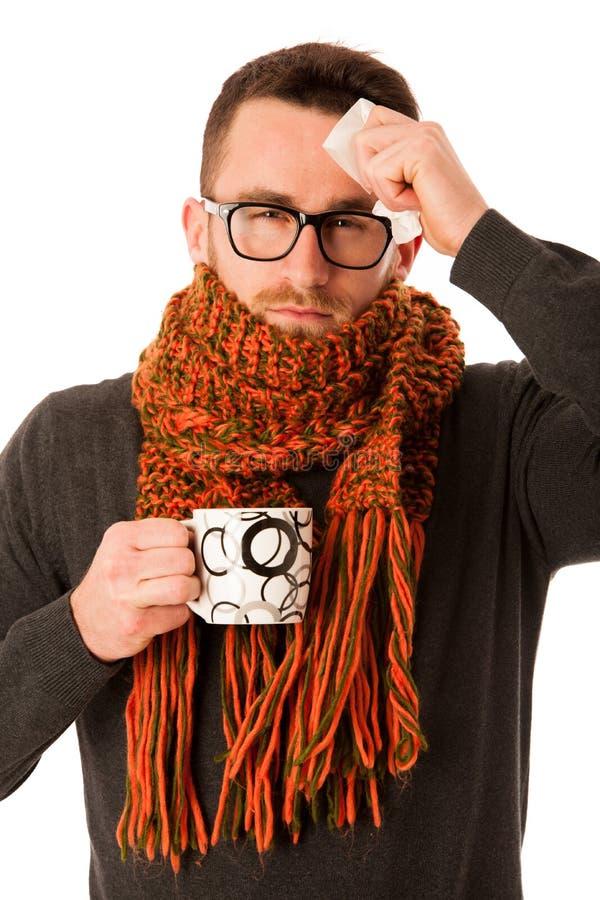 在围巾以流感和热病包裹的人举行杯子愈合t 免版税库存照片