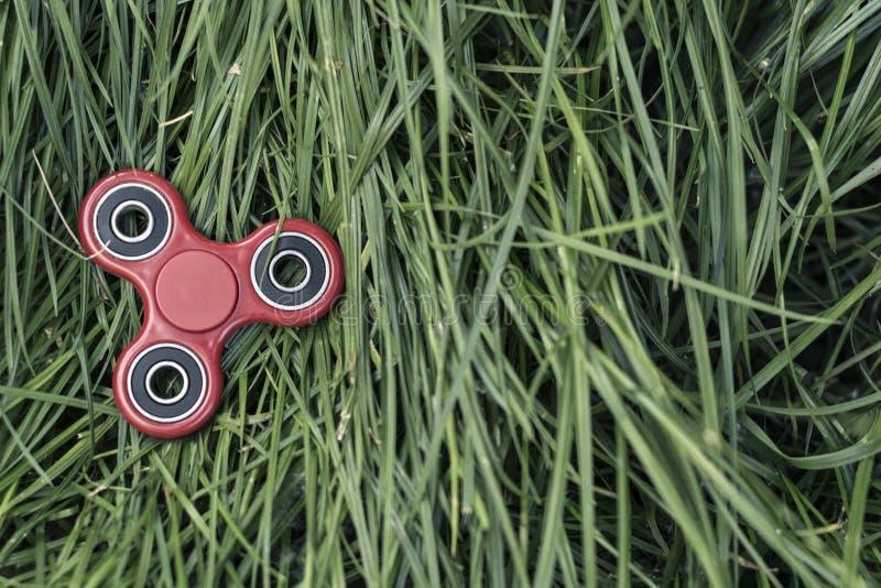 在2017年普遍的红色锭床工人小配件以绿草为背景 库存照片