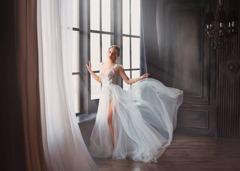 在2019年毕业生,长的白光柔和的飞行的礼服的女孩的华美的图象有光秃的腿的单独站立,天鹅 库存照片