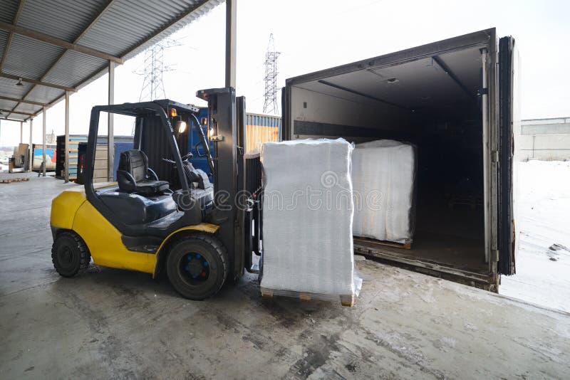 在仓库装货箱子的铲车到户外汽车里 免版税库存图片