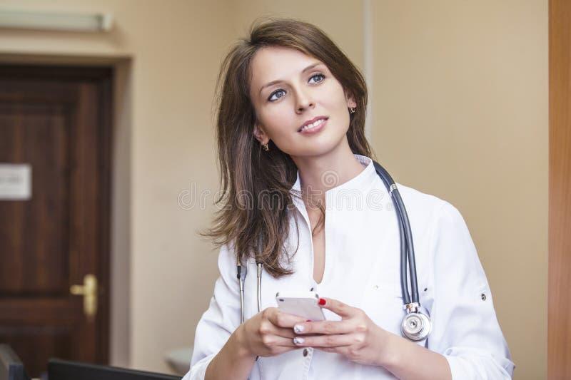 在年轻患者里屋子白色制服的医治妇女 免版税库存照片