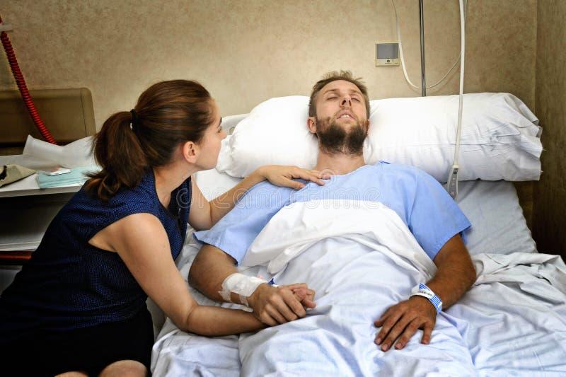 在医房的年轻夫妇供以人员在床举行他手关心的担心的妇女 免版税库存图片