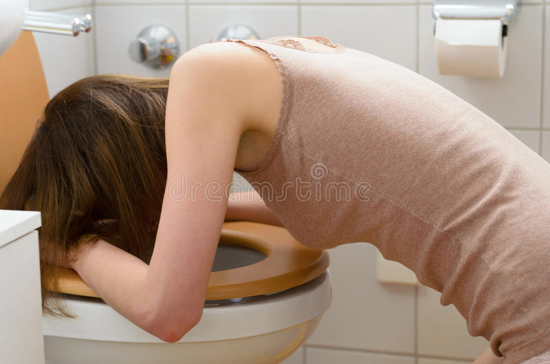 在洗手间前面的病的妇女 库存图片
