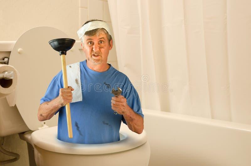在洗手间里面的幽默水管工与工具和卫生纸 库存图片