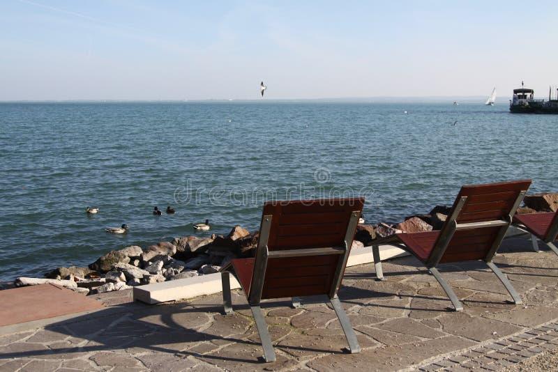 在巴拉顿湖岸的空的轻便折叠躺椅  免版税库存照片
