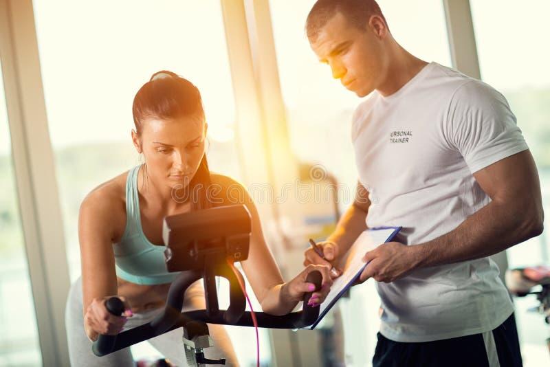 在给指示和帮助的健身房的个人教练员attr 免版税库存图片