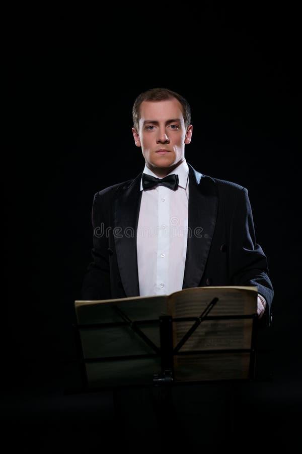 在黑无尾礼服的管弦乐队指挥在黑暗的演播室 免版税图库摄影