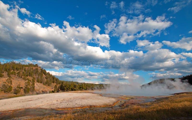 在黄昏cloudscape下的细刨花喷泉在Firehole河旁边的中途喷泉水池黄石国民同水准的 图库摄影