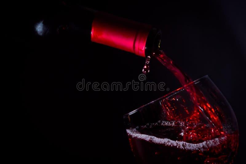 在黑暗的光的倾吐的红葡萄酒玻璃 免版税库存图片