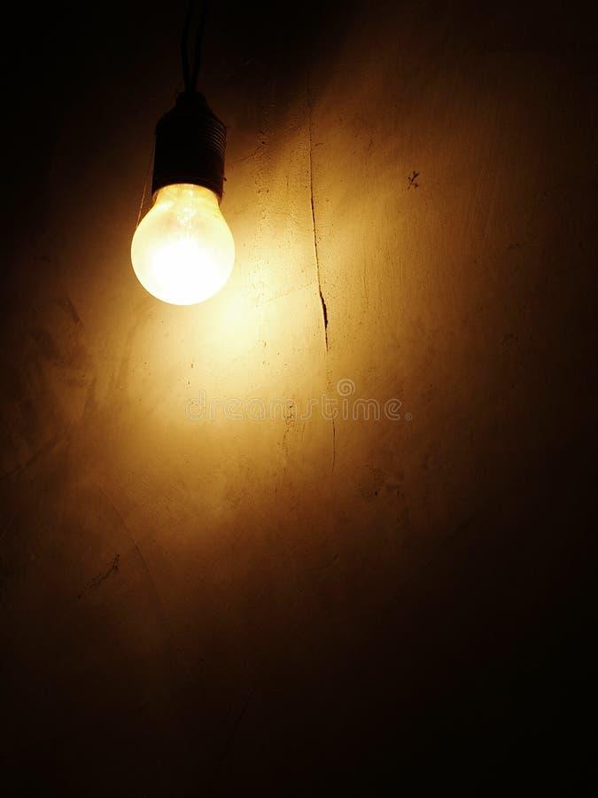 在黑暗的墙壁上的电灯泡 免版税图库摄影