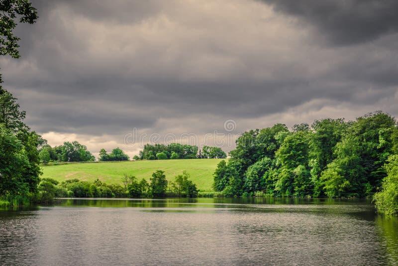 在黑暗的多云天气的湖风景 库存图片