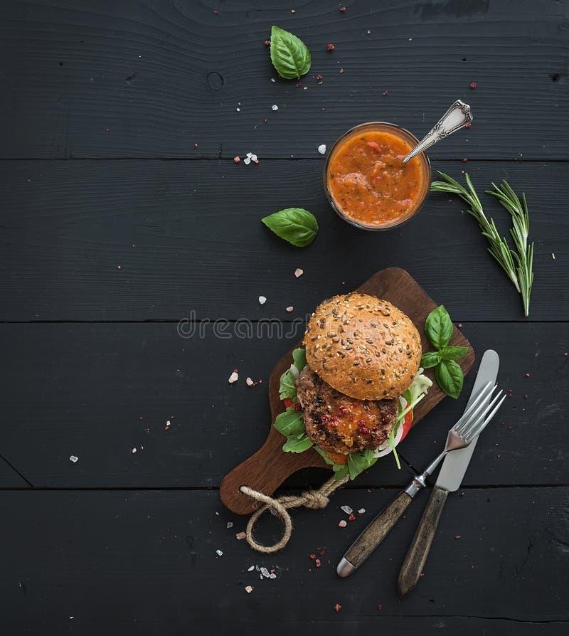 在黑暗的服务板的新鲜的自创汉堡与 免版税图库摄影