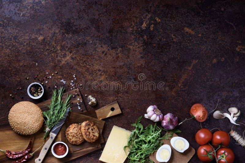 在黑暗的服务板的新鲜的自创汉堡用牛肉、蕃茄、乳酪和鸡蛋在黑暗的背景 顶视图,拷贝空间 免版税库存图片