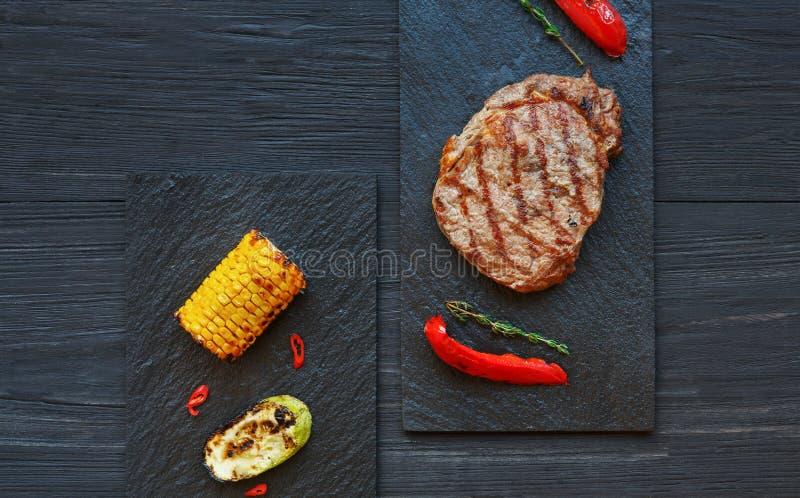 在黑暗的木桌背景,顶视图的烤牛排 免版税库存图片