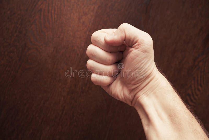 在黑暗的木背景的强的男性拳头 免版税库存照片