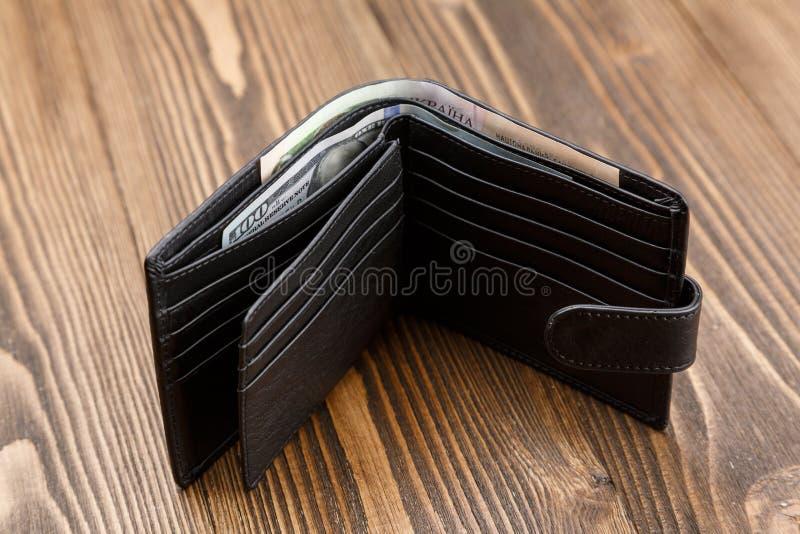 在黑暗的木背景的新的黑皮革钱包 图库摄影
