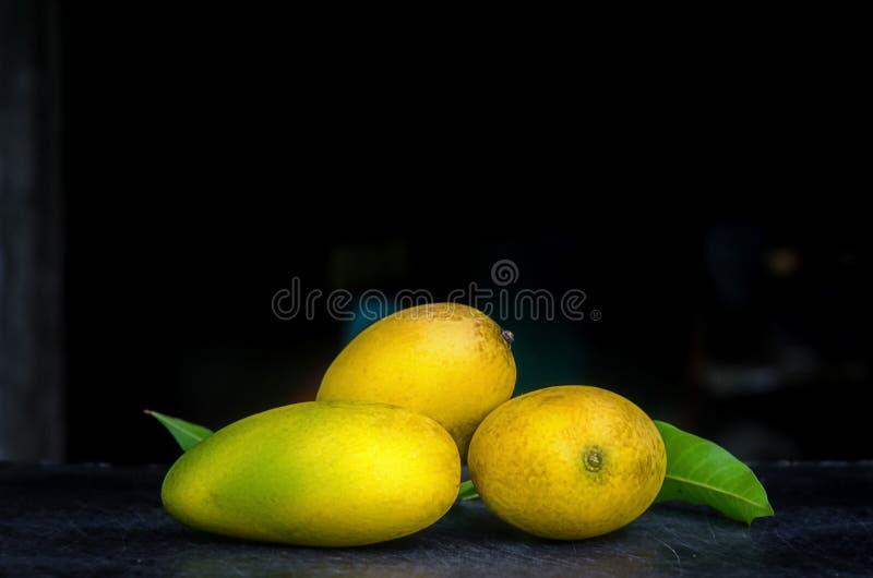 在黑暗的桌和木地板上的芒果 图库摄影