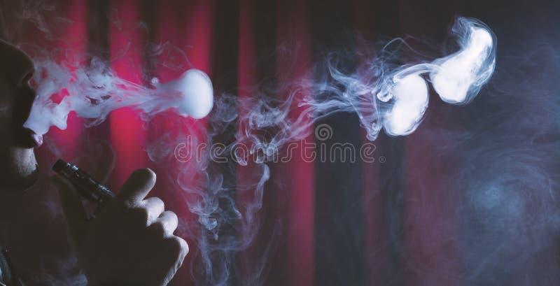 年轻在黑暗的背景的人vaping的云彩 免版税库存图片