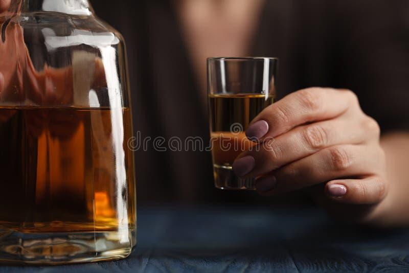 在黑暗的背景的妇女饮用的酒精 在酒杯的焦点 免版税库存照片