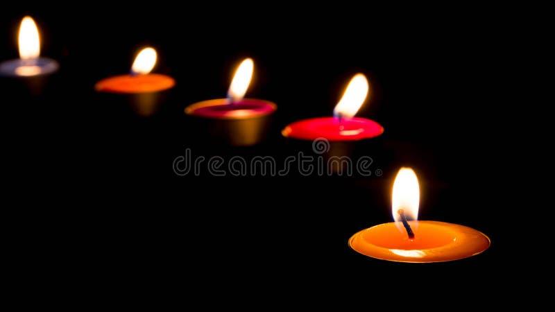 在黑暗的背景的灼烧的蜡烛与温暖的光 免版税图库摄影