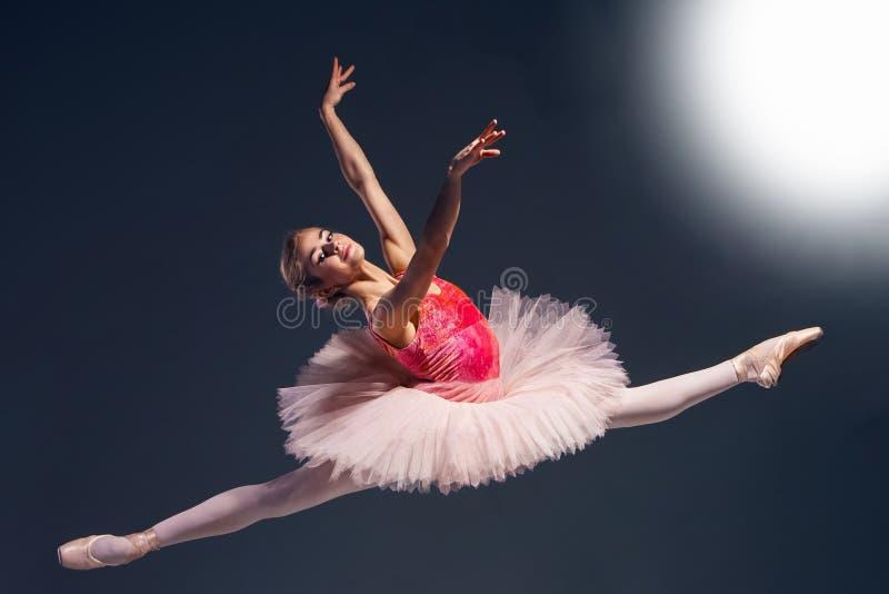 在黑暗的背景的美丽的女性跳芭蕾舞者 芭蕾舞女演员穿桃红色芭蕾舞短裙和pointe鞋子 免版税库存照片