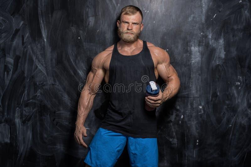 在黑暗的背景的肌肉爱好健美者人 免版税库存图片