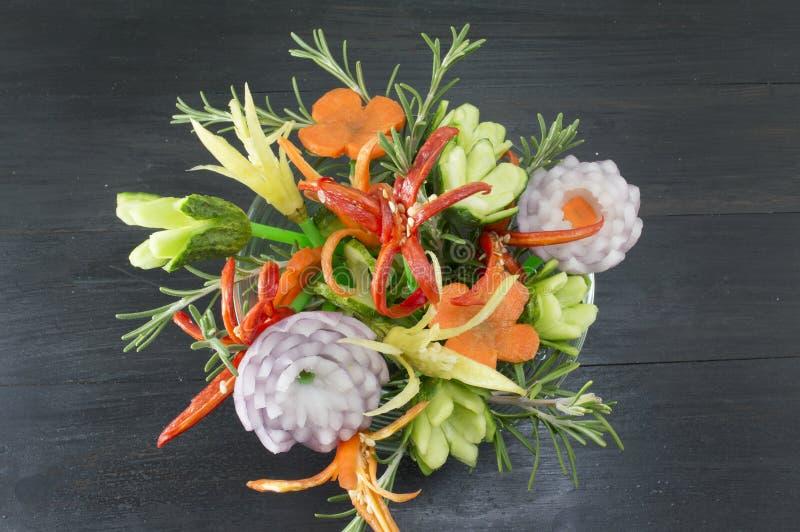 在黑暗的背景的花形状的菜沙拉 免版税库存图片
