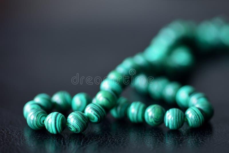 在黑暗的背景的绿色绿沸铜项链 免版税库存照片