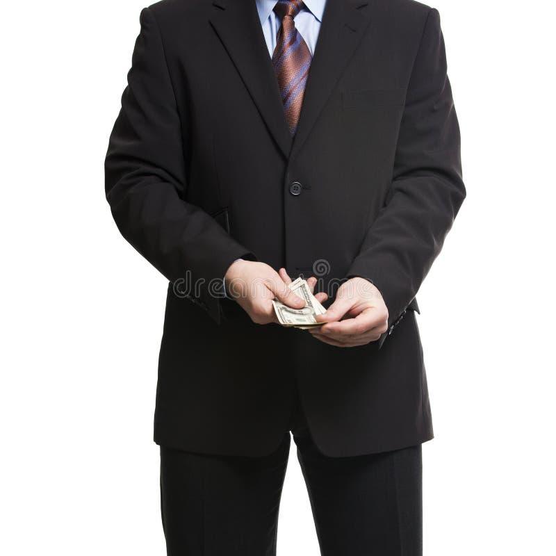 在黑暗的衣服的商人与一束美国美元 免版税库存照片