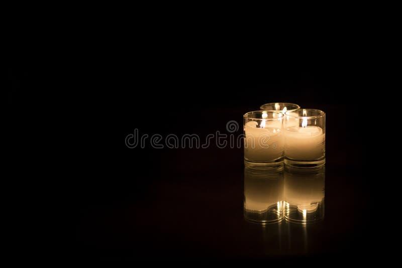 在黑暗的表上的三个蜡烛 图库摄影