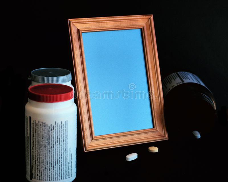 在黑暗空的照片框架,药片,医学瓶 库存图片