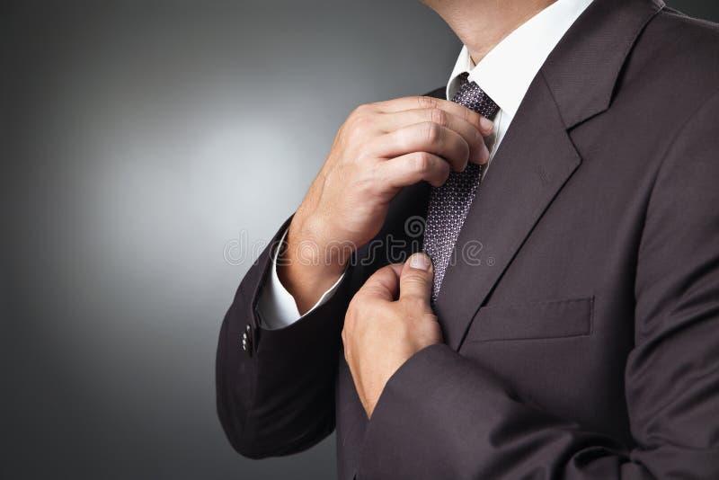 在黑服装领带的商人你的领带 免版税库存照片