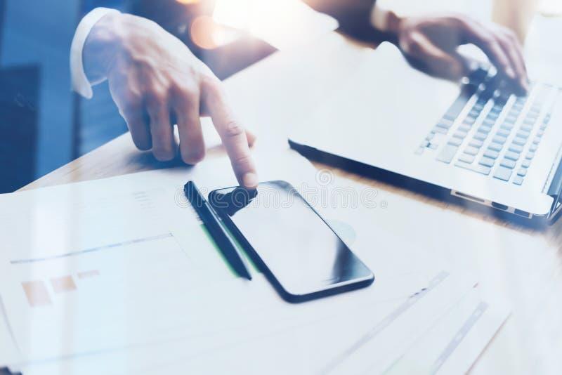 在晴朗的办公室供以人员研究现代手机和膝上型计算机和指向手指智能手机家庭按钮  图库摄影