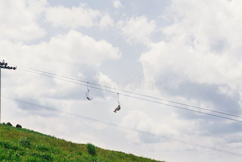 在晴朗的夏天山的老驾空滑车卷扬机在蓝天下和 库存照片