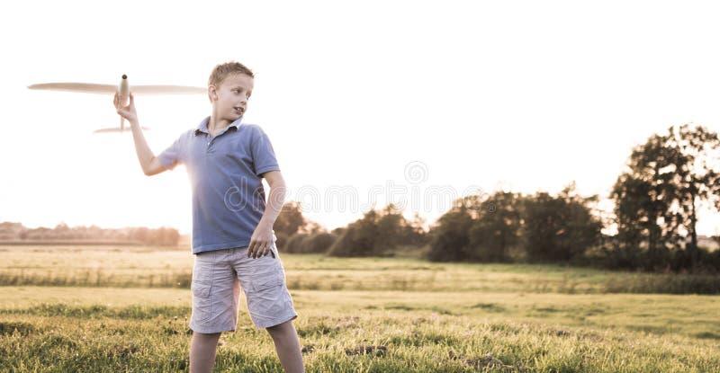 在晴朗的背景的男孩投掷的飞机 免版税库存照片