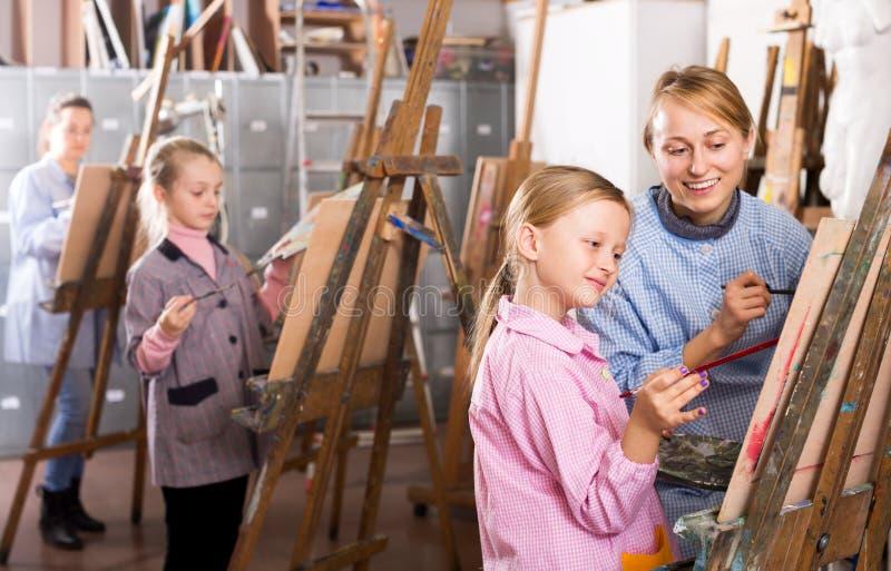 在绘画类期间的女老师帮助的女孩 免版税库存照片