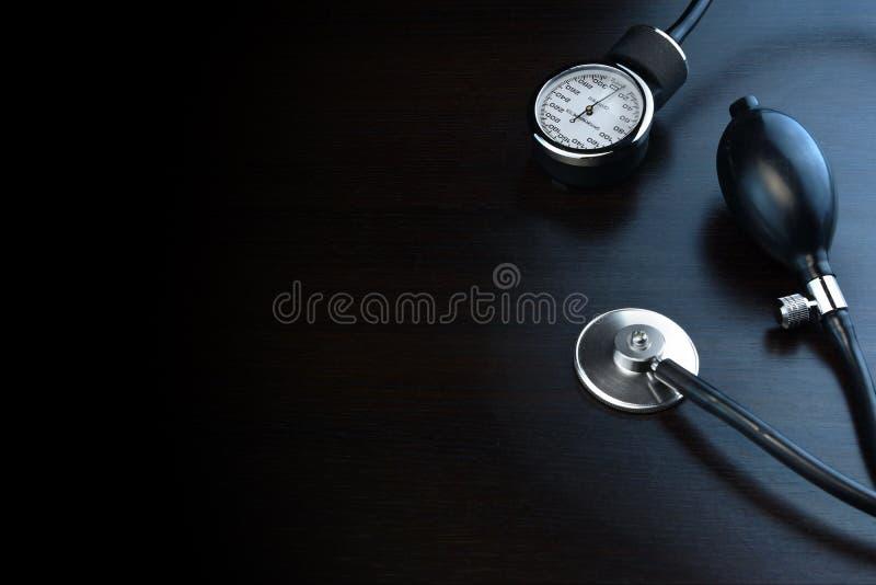 在黑木背景后面的心脏病学医疗设备 图库摄影