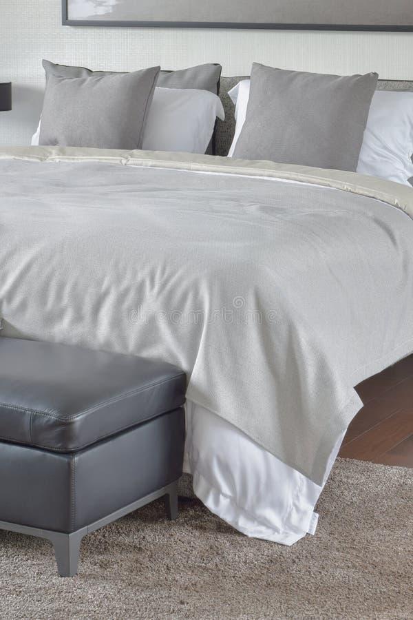 在轻松的床上的米黄毯子与黑皮革无背长椅在卧室 免版税图库摄影