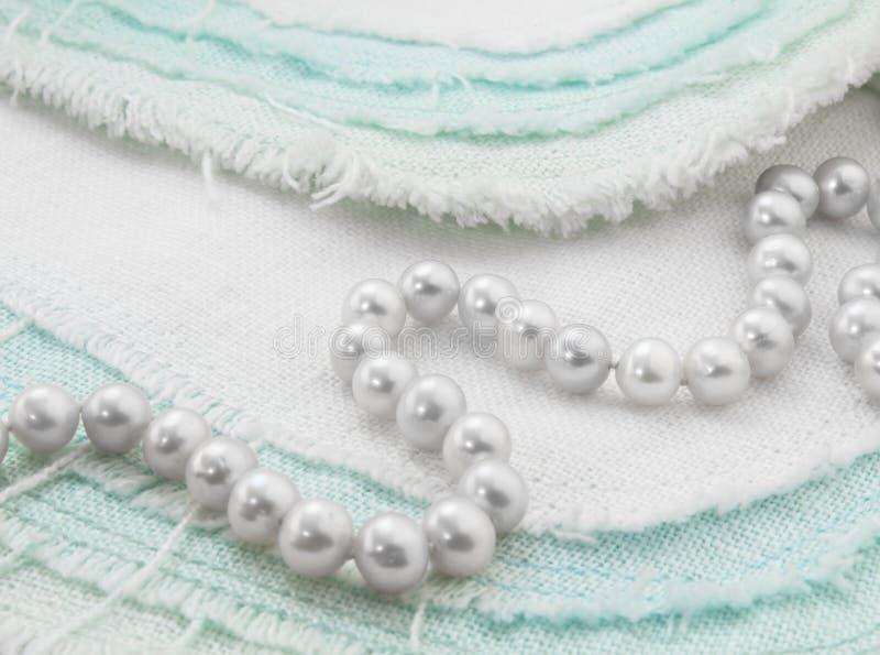 在绿松石和白色的白色珍珠项链特写镜头磨损了亚麻布 库存照片