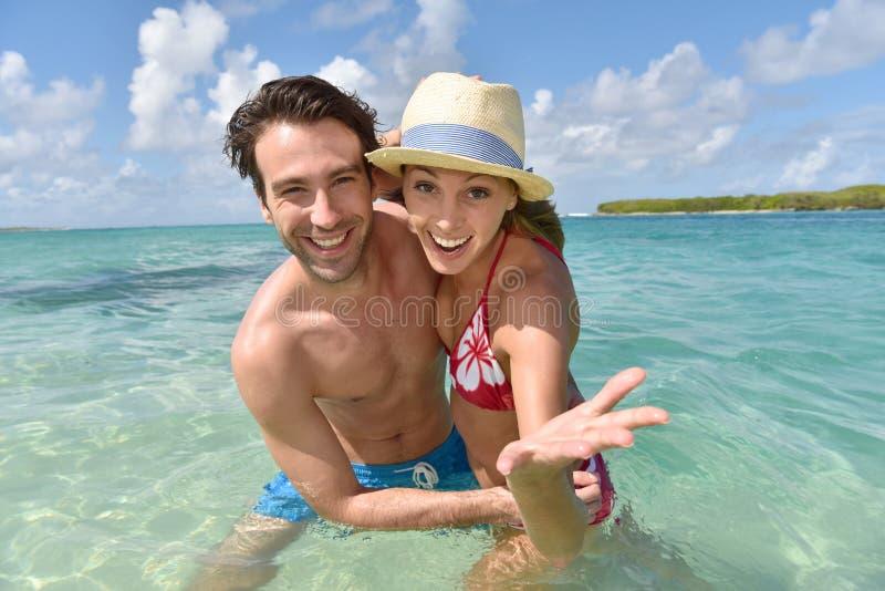 在绿松石海水的快乐的夫妇 库存照片