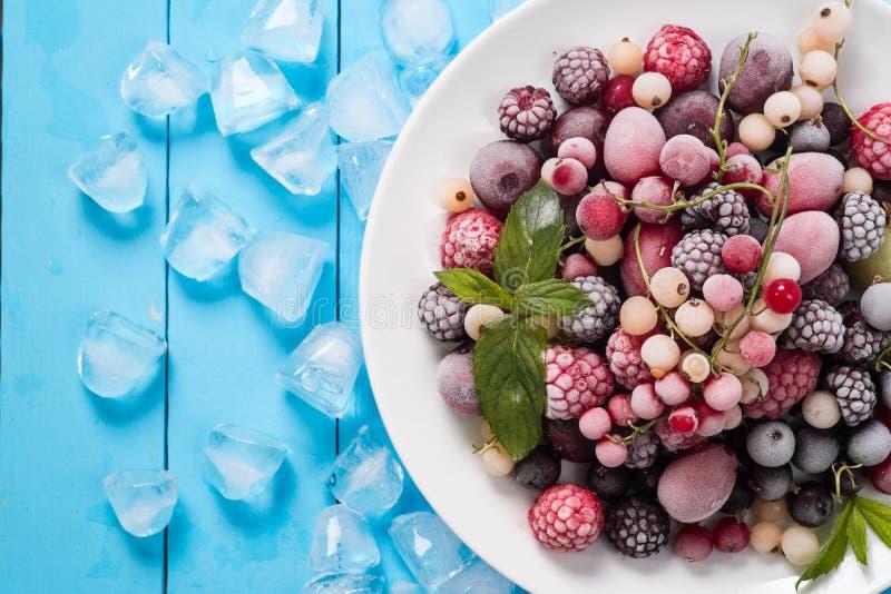 在绿松石背景顶视图的冷冻莓果 免版税库存照片