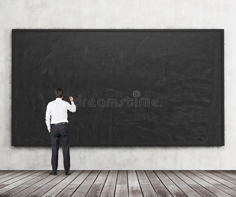 在黑黑板写某事人的背面图 木楼层和混凝土墙 乞求的概念 免版税图库摄影
