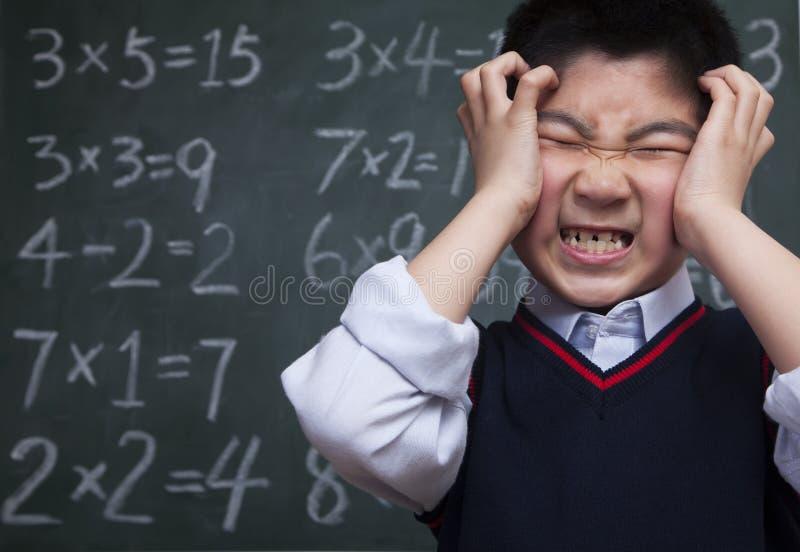 在黑板前面的男小学生有头的在他的手上 库存照片