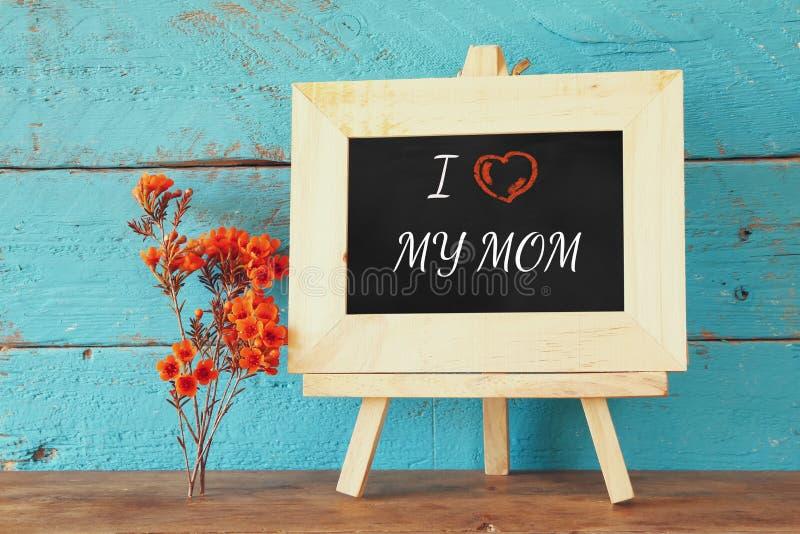 在黑板旁边的花有词组的:我爱我的妈妈,在木桌上 愉快的母亲节概念 免版税库存照片