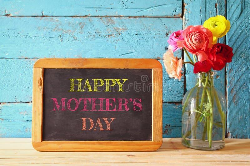 在黑板旁边的花,在木桌上 母亲节concep 库存照片
