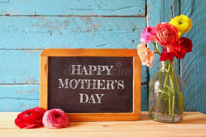 在黑板旁边的花 愉快的母亲节概念 免版税库存图片