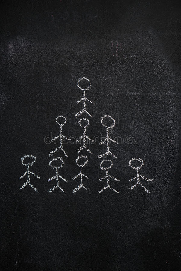 在黑黑板的人的队金字塔 库存图片
